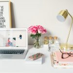 love business MacBook Air beside gold-colored study lamp and spiral books